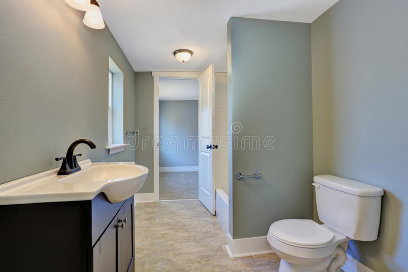 Blue bathroom interior with black vanity cabinet, toilet and tile floor. Northwest, USA royalty free stock images