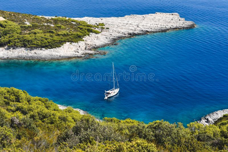 Blue bay with a white sailing boat, Croatia in Europe. Top view of a blue bay with clear blue and turquoise sea water and a white sailing boat anchored by the royalty free stock photography