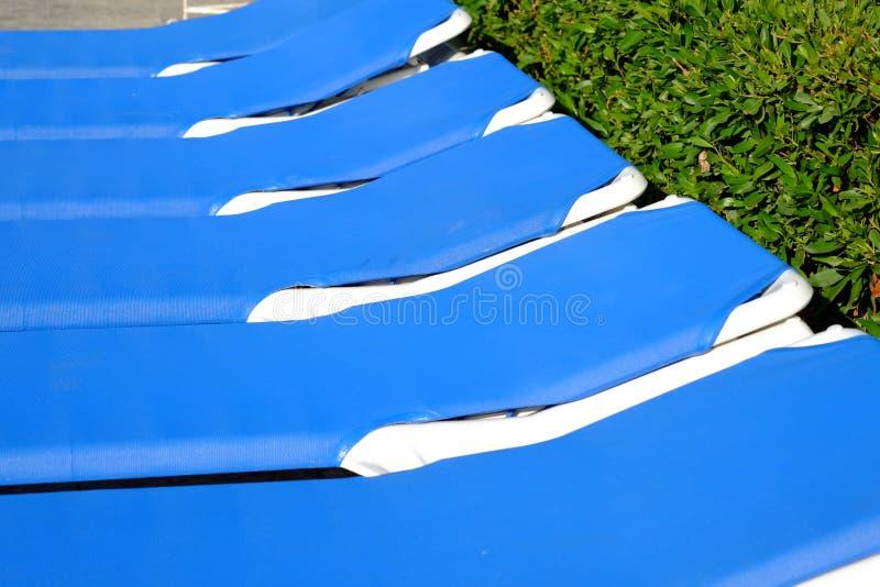 Blue beach chairs and sun umbrella near pool. Travel background stock photos