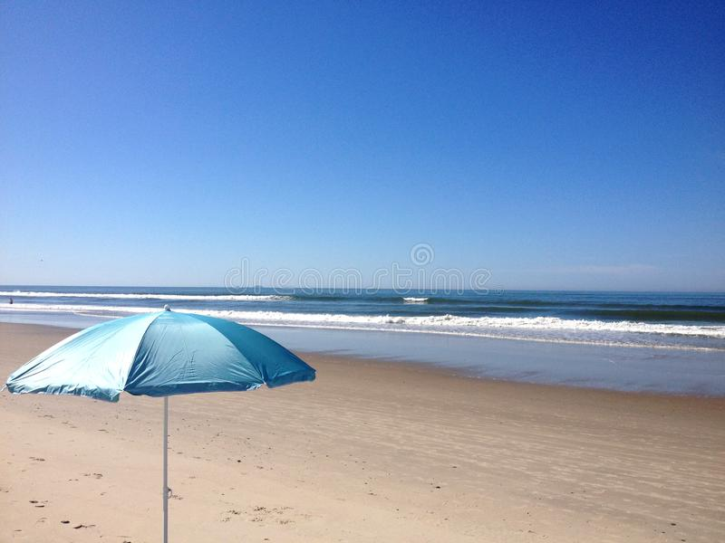 Blue beach umbrella on blue sky. At the beach, Matinhos, Parana, Brazil royalty free stock photos