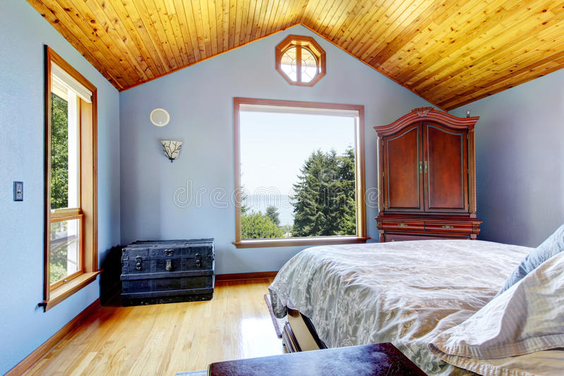 Blue bedroom with wood ceiling and bed interior. Blue bedroom with wood ceiling and bed, large windows interior stock photos