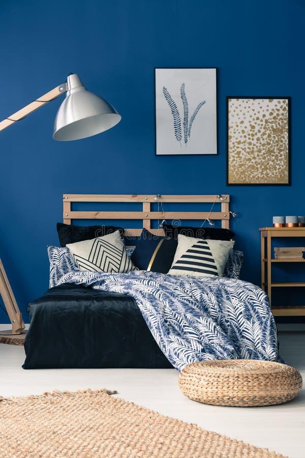 Blue bedroom with wooden furniture. Elegant dark blue bedroom with wooden furniture and wicker pouf stock image