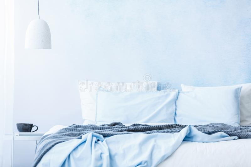 Blue bedsheets and pillows on bed next to a table with a cup under white lamp in simple bedroom interior stock photo
