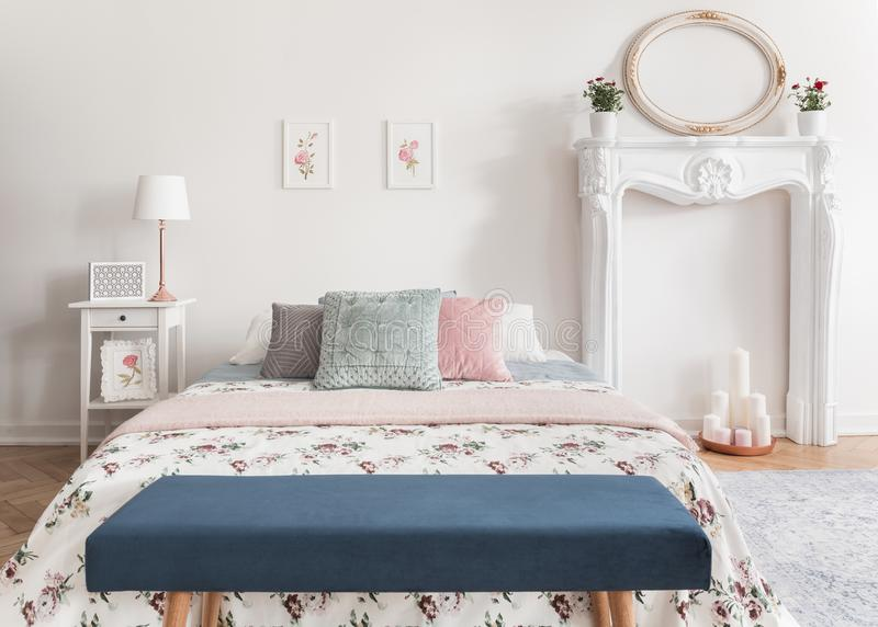 Blue bench in front of patterned bed with pastel cushions in white bedroom interior with mirror. Real photo royalty free stock photos