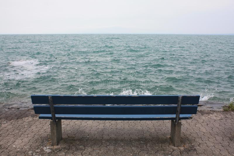 Blue bench on the lake in Switzerland. royalty free stock photography