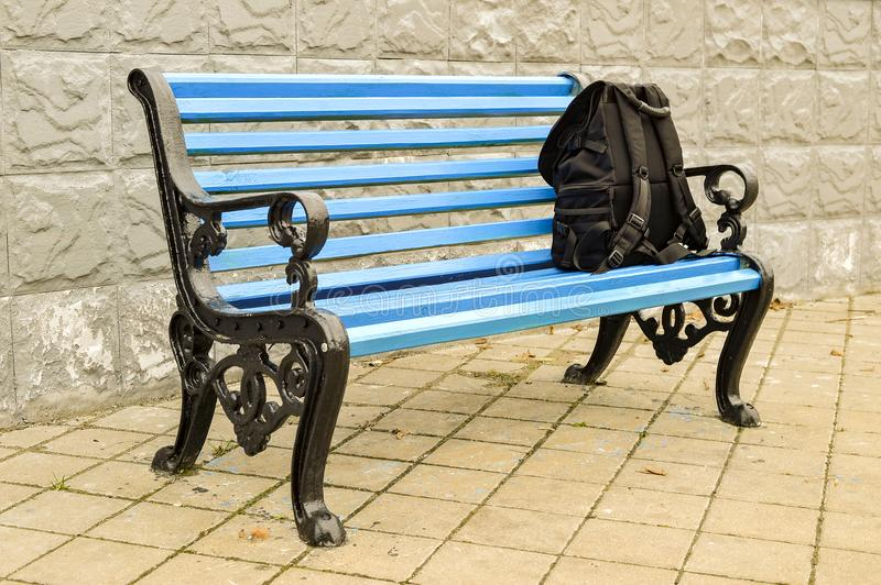 The blue bench in the Park on the tiled pavement with a black backpack. No body. stock image
