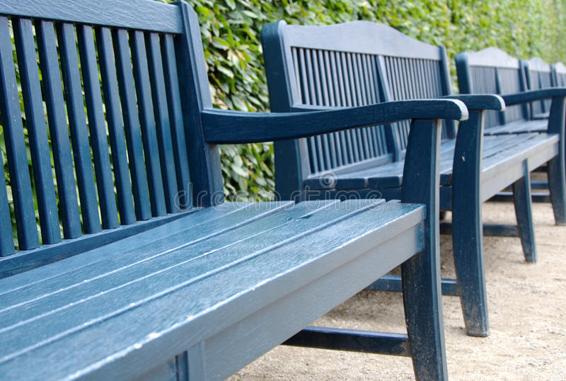 Blue benches in a row with green bush in the background stock photography