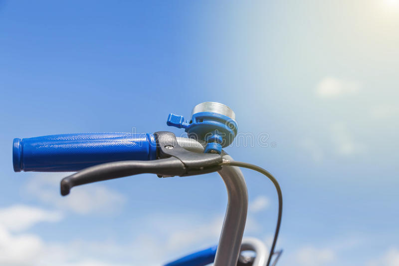 Blue bicycle bell with blue grip on handle bar. On blue sky background stock photography