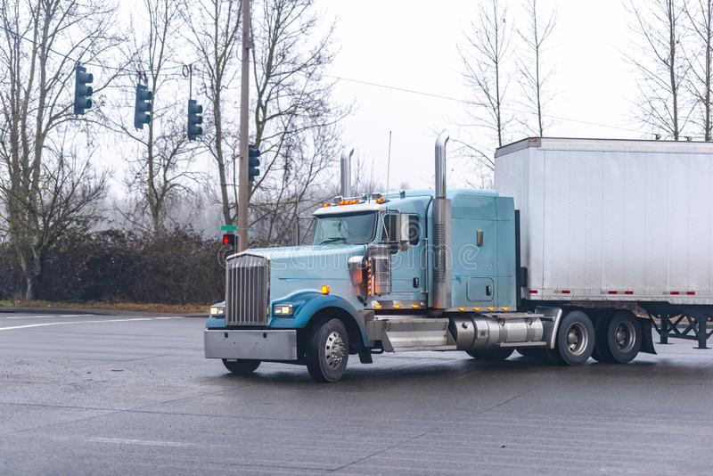 Blue big rig classic American semi truck with turned on headlights transporting cargo at semi trailer turning on wet crossroad. Blue big rig classic American stock photos