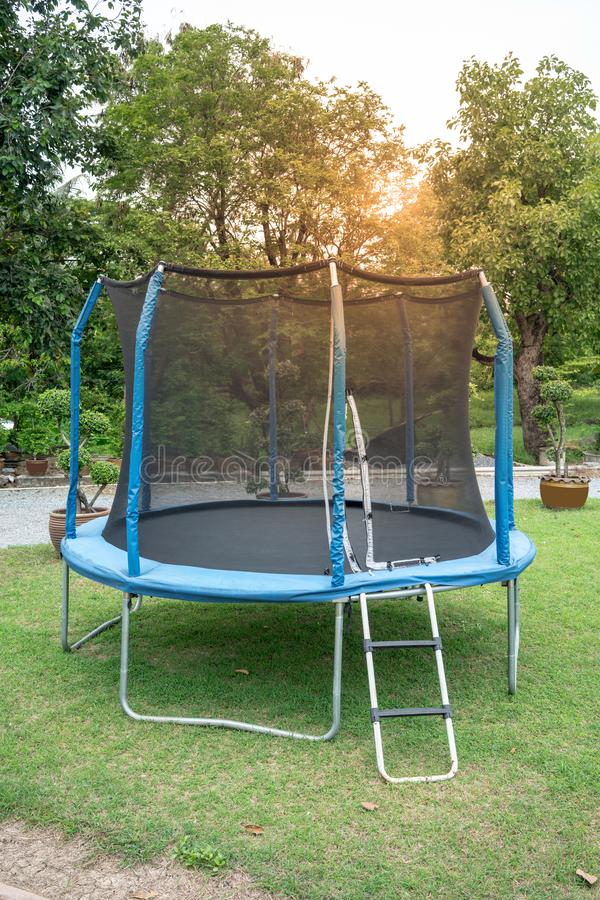 Blue big Trampoline on the green grass. Outdoor Trampoline with royalty free stock image