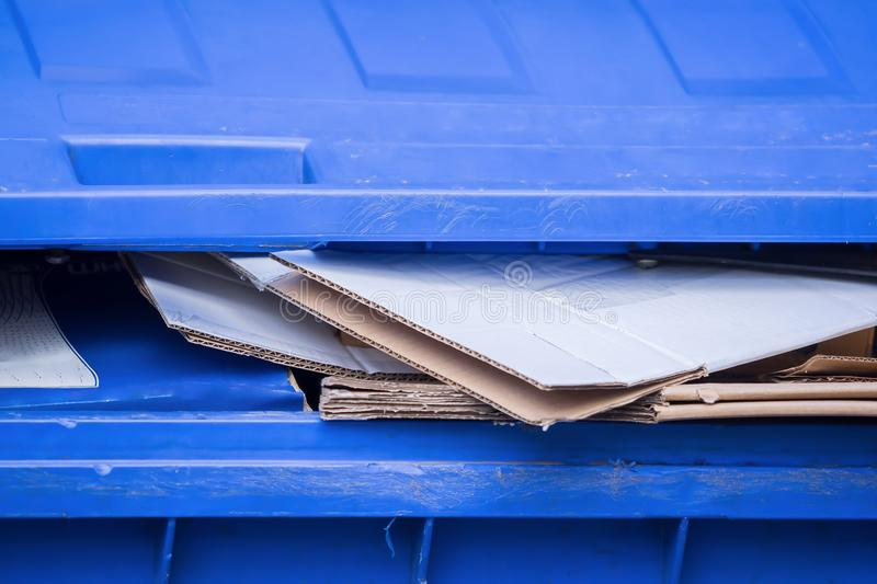A blue bin for old paper and cardboard boxes royalty free stock image