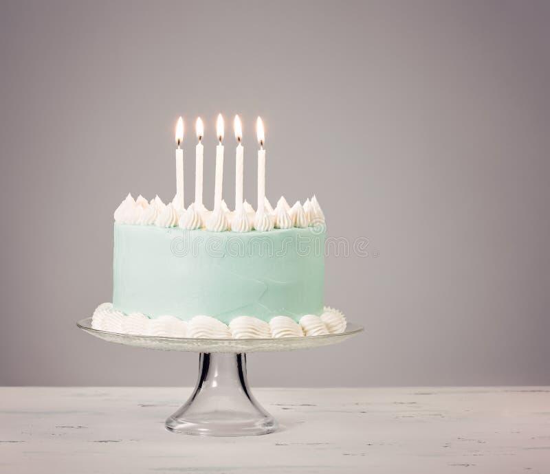Blue Birthday Cake over grey Background. Bllue birthday cake over grey background with white candles stock image