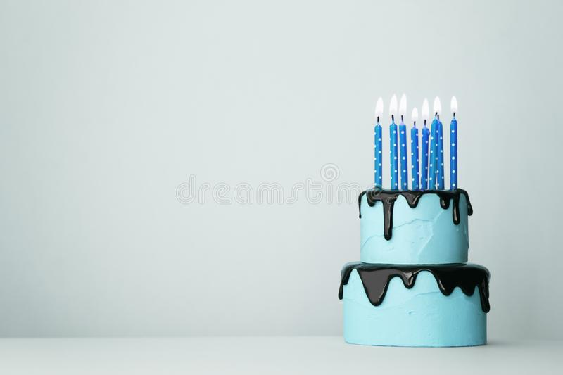 Blue birthday cake. Blue tiered birthday cake with eight candles royalty free stock photography