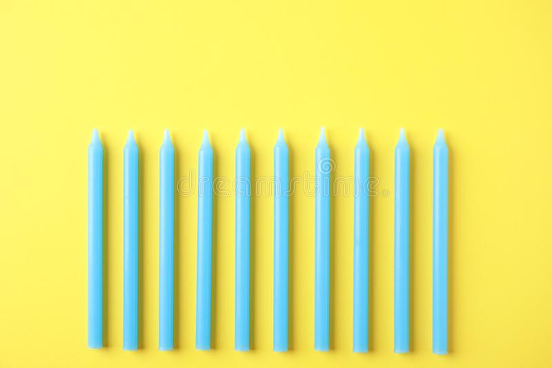 Blue birthday candles on yellow background. Top view royalty free stock photos