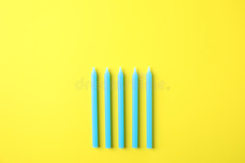 Blue birthday candles on yellow background. Top view stock photos