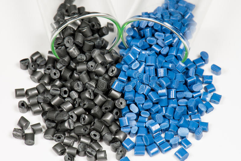 Blue and black polymer pellets in test tubes royalty free stock photo