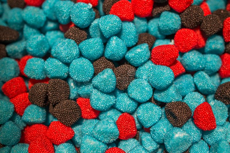 Blue black and red candies in the form of raspberries and blackberries stock image