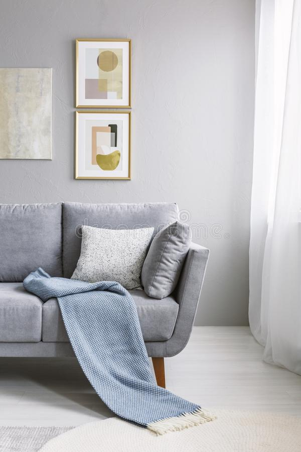 Blue blanket on grey couch against the wall with gold paintings. In living room interior. Real photo stock photos