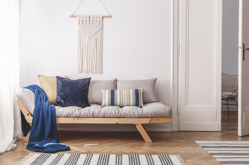 Blue blanket and pillows on grey wooden couch in white living room interior with door. Real photo. Concept stock photos
