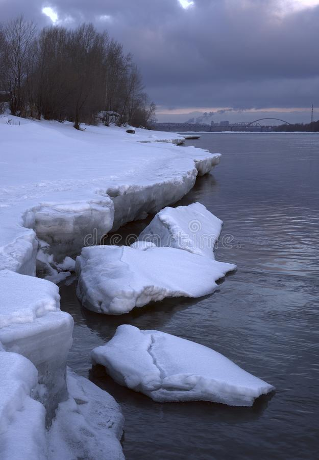 The ice shards on the Bank of Obi - vertically. Blue blocks of ice broke away from the shore on the opened river early . Morning in silvery blue tones. Bridge stock image