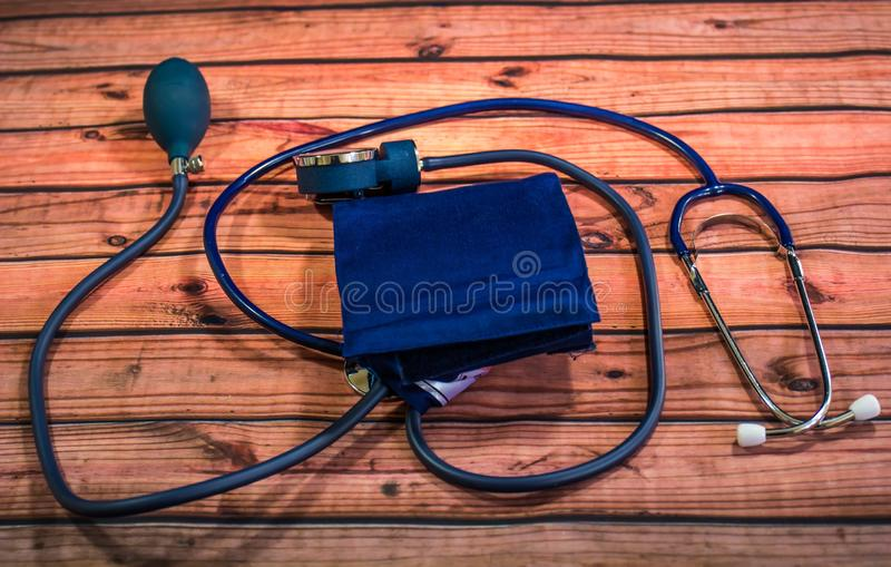 Blood Pressure Cuff And Stethoscope. Blue Blood Pressure Cuff, Stethoscope And Bulb With Release Valve On Wooden Table stock image