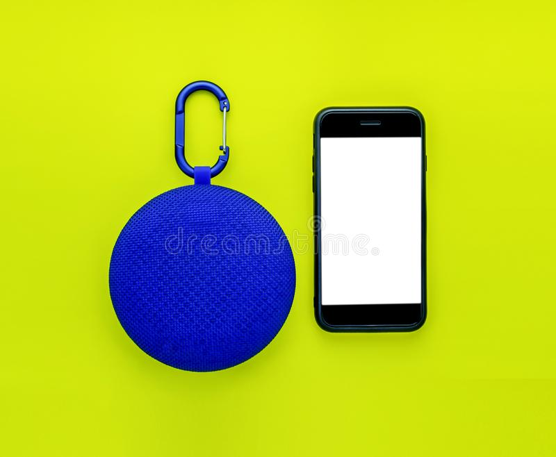 Blue bluetooth speaker and mobile phone or smartphone  mock up on yellow background, business technology concept royalty free stock photography