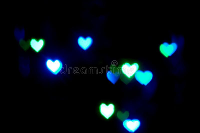 Blue blurred lights in the shape of hearts in the dark stock photo
