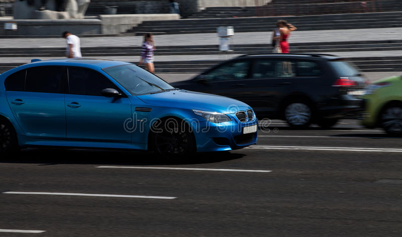 Blue BMW in city stock images