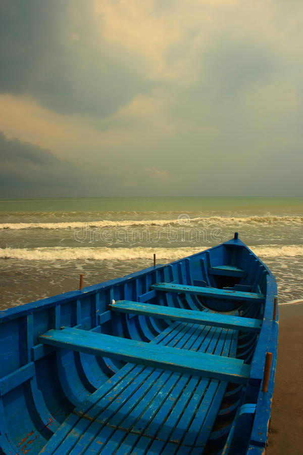 Blue boat. A blue boat waiting on the shore for the storm to clear stock images