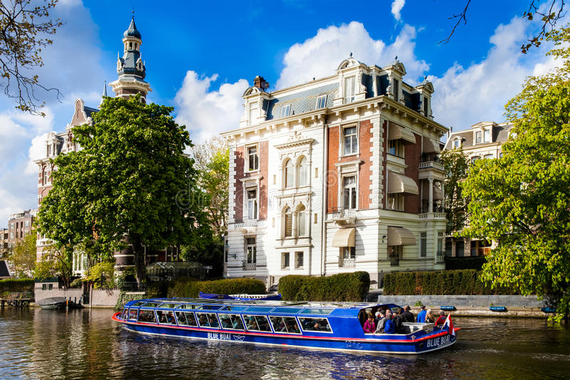 Blue boat company canal trip in Amsterdam city, Netherlands stock image