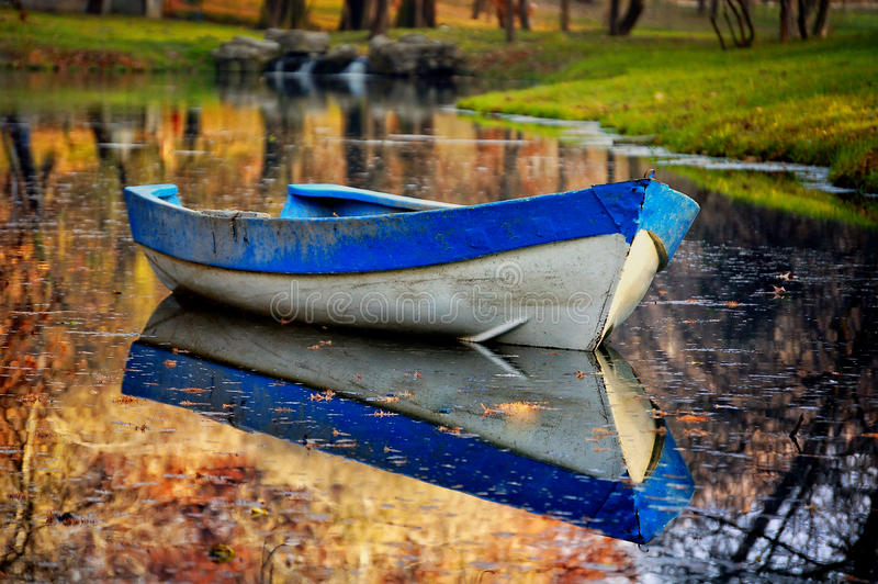 Blue boat on the lake in autumn forest. Colorful autumn landscape. Nature background. Blue boat on the lake in autumn forest. Old wooden boat on the lake bank stock image