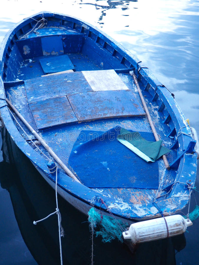 Blue Boat, Pozzuoli Harbor. Evening scene in Pozzuoli, Italy. Blue boat rests in the calm reflective water stock photography