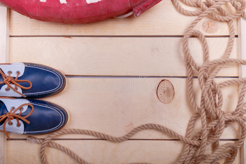 Blue boat shoes on wooden background near lifebuoy and rope. Top view. Copy space. stock image