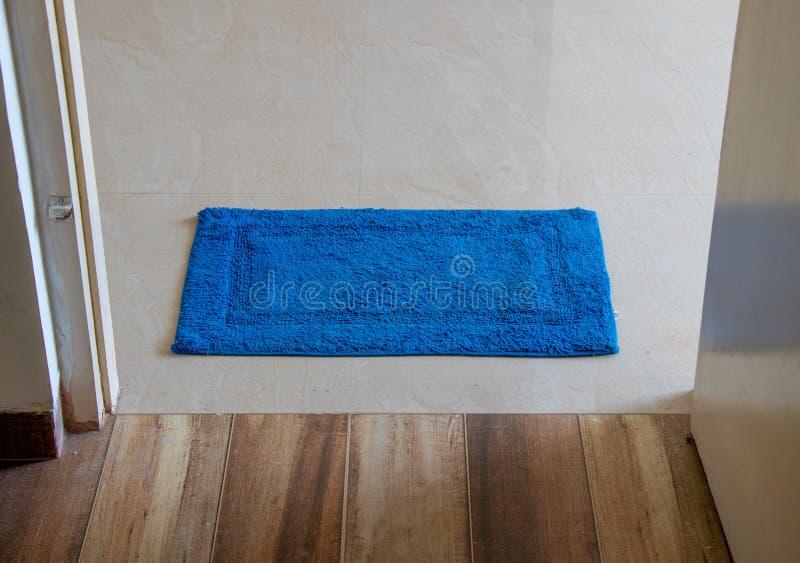 Blue boor mat. Blue door  mat lying in door royalty free stock photos