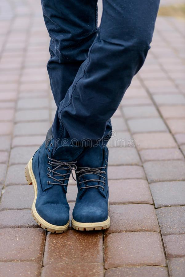 Blue boots on men`s legs in blue jeans royalty free stock photo