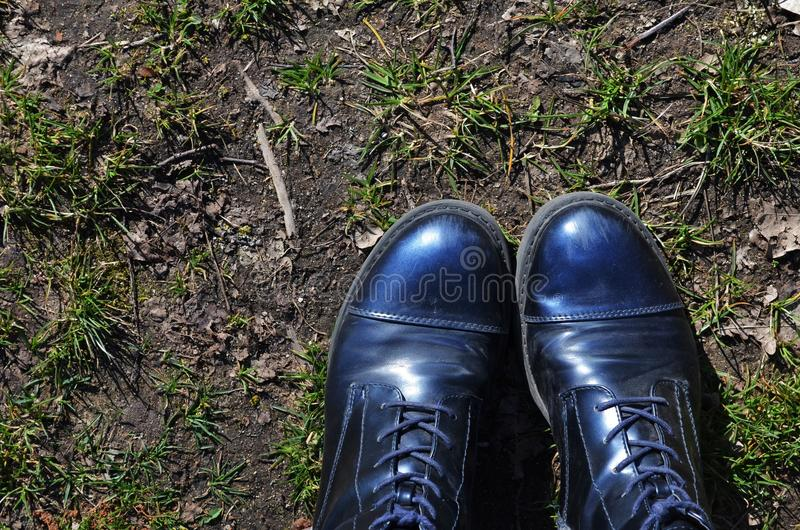 Blue boots standing on dirty ground in a forest. While fresh grass starts to grow royalty free stock photography