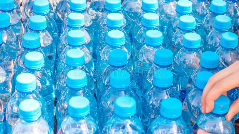 Blue bottles with pure clear water prepared for drinking. The hand takes one bottle royalty free stock images