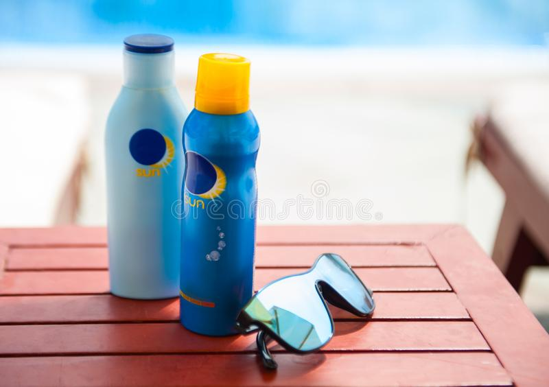 Blue Bottles sunscreen with sunglasses on the table. Swimming pool. Sunglasses with sunscreen bottles on the wooden table near the swimming pool. Summer rest royalty free stock image