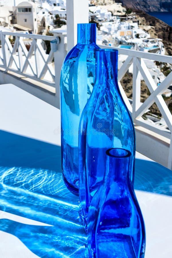 Blue bottles on white Cycladic terrace in Santorini, Greece stock images