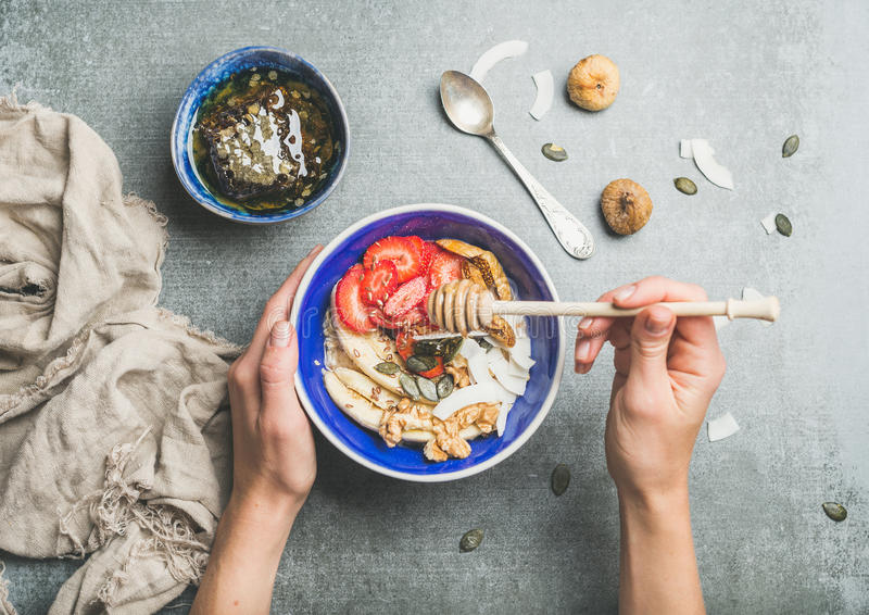 Blue bowl with healthy vegetarian breakfast ingredients in woman`s hands. Healthy breakfast bowl. Yogurt, granola, seeds, fresh and dry fruits and honey in blue stock photography