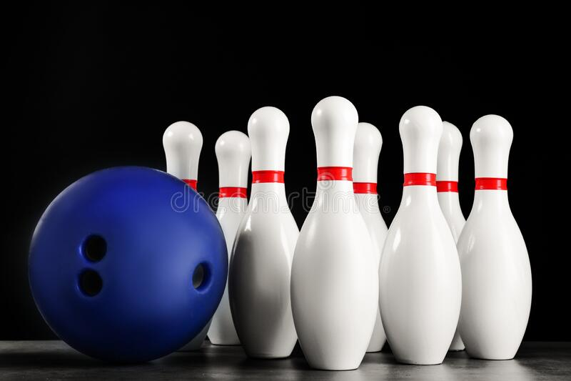 Blue bowling ball and pins on stone table. Blue bowling ball and pins on grey stone table royalty free stock photos