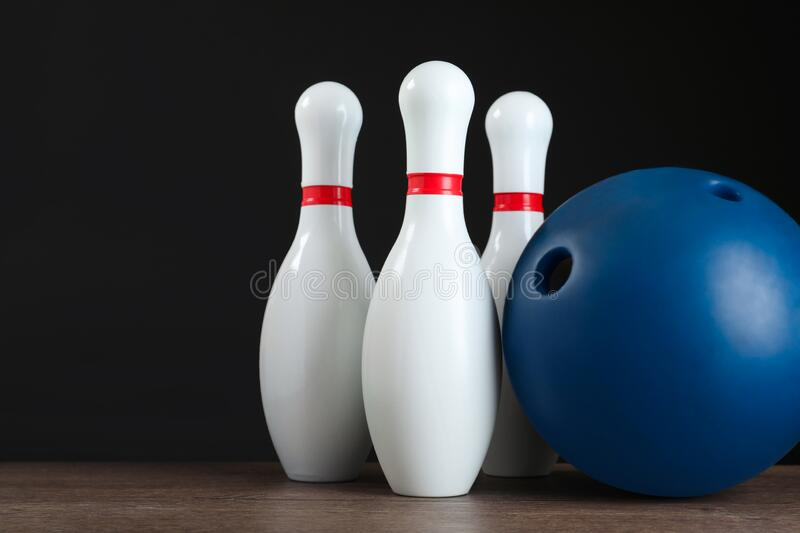 Blue bowling ball and pins on table. Blue bowling ball and pins on wooden table stock photo