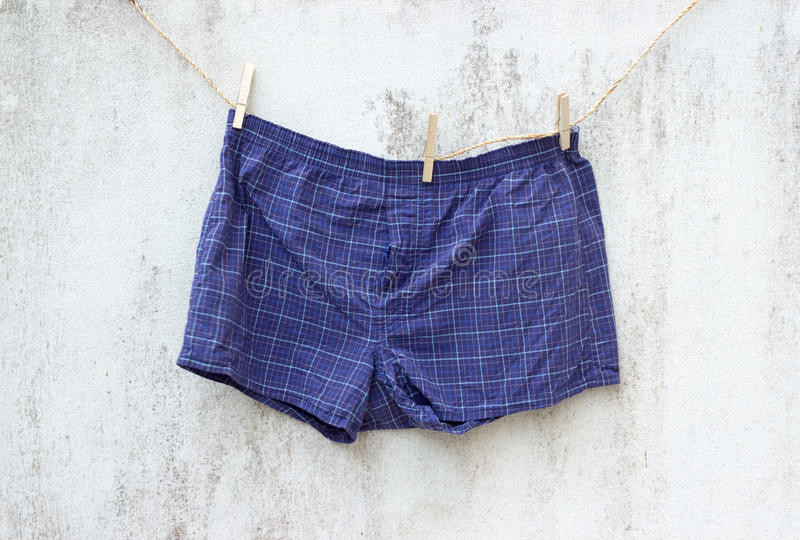 Blue boxer underwear on grunge wall stock photography