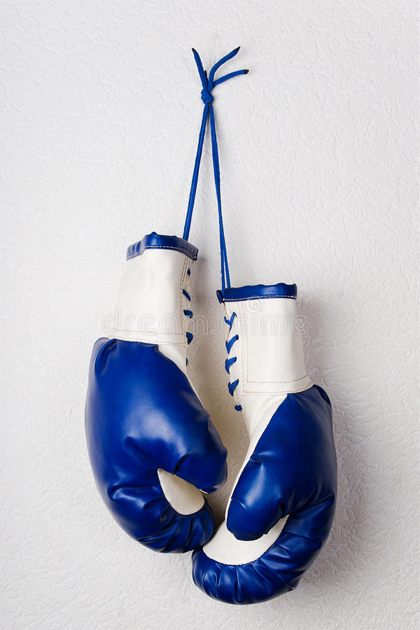 Blue boxing gloves. White-and-blue boxing gloves hanging on a white wall stock photos