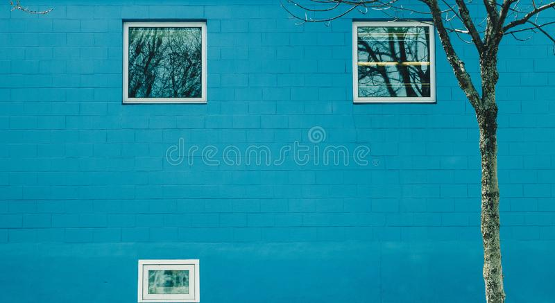 Blue brick wall with 3 windows stock photography