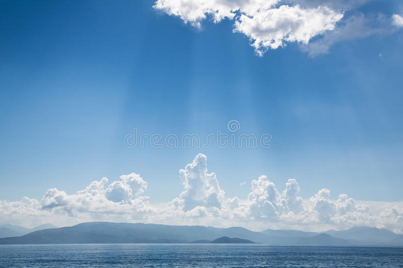 Blue bright sky background on the ocean with clouds and emotional mood for dreams, mourning, death concepts. royalty free stock photography