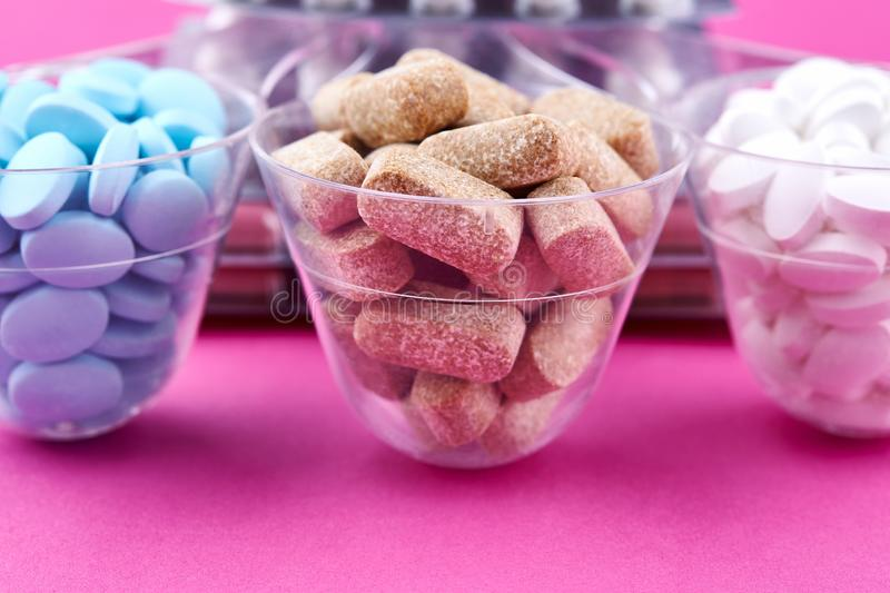 Blue brown and white pills in graduated glass on pink background royalty free stock image