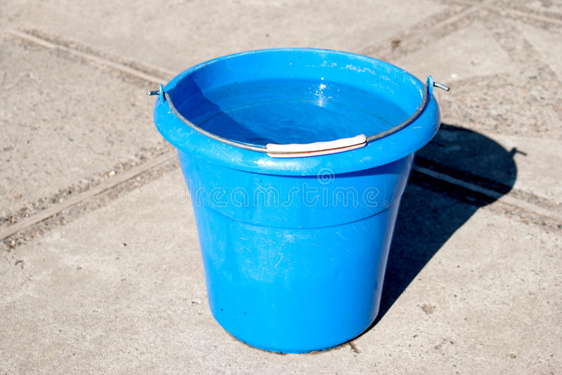 Blue bucket. With fresh water on the ground royalty free stock photo