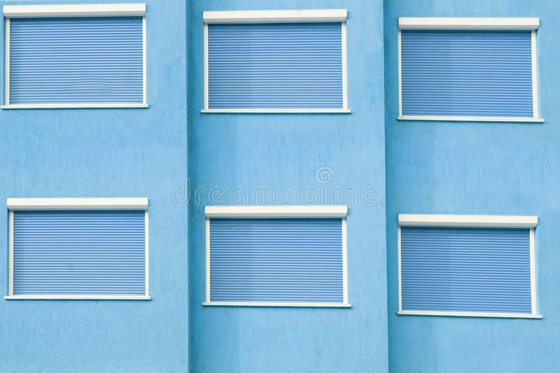 Blue Building Facade with Six Closed Windows Shutters. Background with Space for Text or Image stock photos