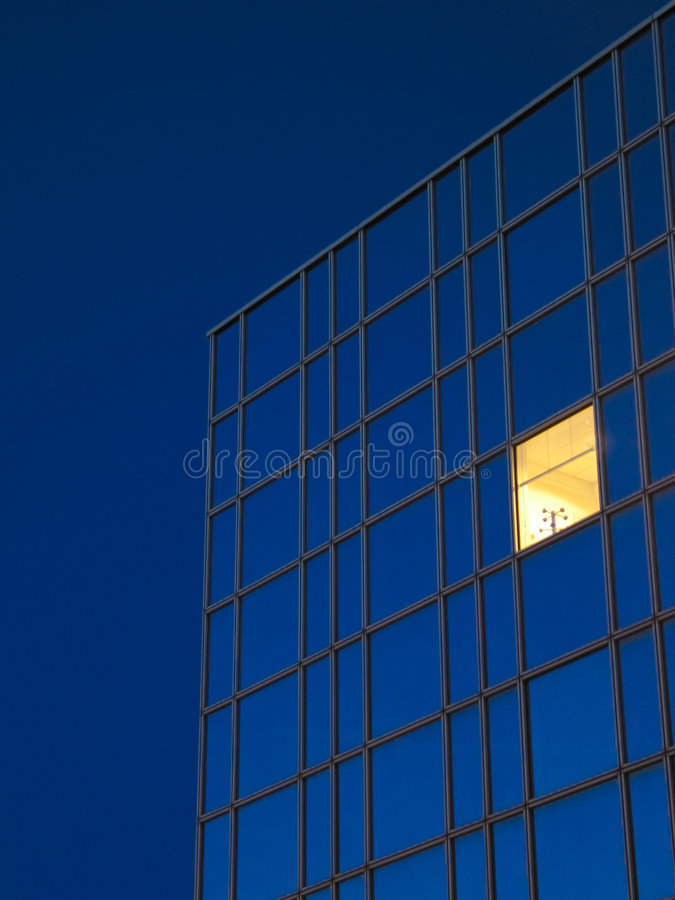 Blue Building Yellow Window. A yellow window in a royal blue office building against a royal blue sky royalty free stock images